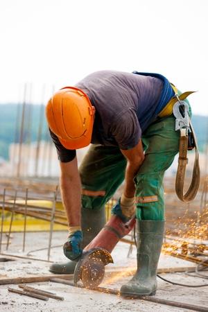 Builder worker sawing metal at construction site Standard-Bild