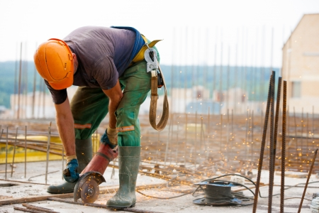 construction work: Industrial worker cutting metal rebar at construction site w Stock Photo