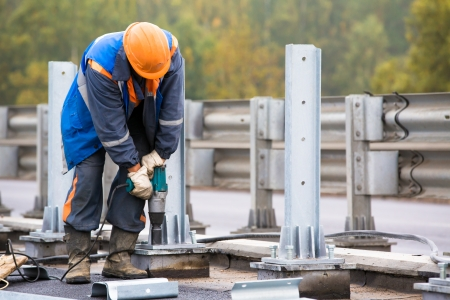 Laborer worker tightening bolts with Electric Impact Wrench tool during construction road works on installation traffic barrier Standard-Bild