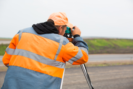 Industrial worker making measuring with theodolite