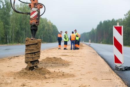 Boormachine boren van gaten in de grond tijdens de bouw wegenwerken Stockfoto