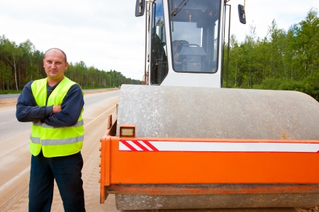 Heavy vibration roller and industrial worker during road construction Stock Photo - 24635894