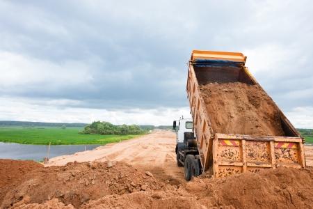 ダンプ トラックの荷を下す土壌や砂道路工事中、工事現場
