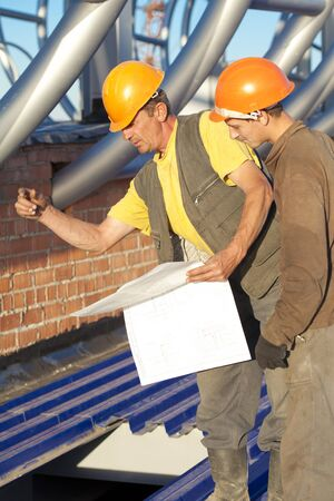 Industrial workers with blue print during construction works photo