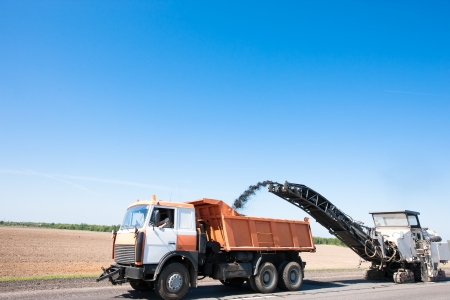 Milling machine loading crushing Asphalt into Dump Truck during repairing road works Stock Photo