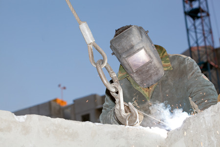 Industrial worker Welder welding metal rebar in reinforced concrete panels during hoisting construction works photo