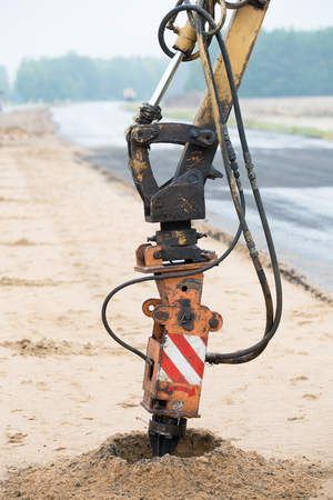boring rig: Drilling rig boring holes in soil during construction road works Stock Photo