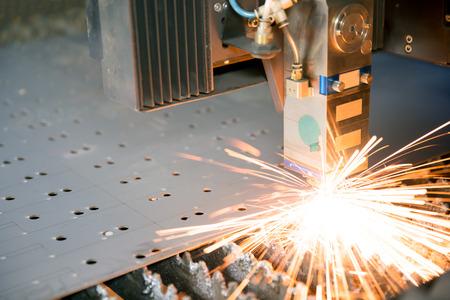 Industrial laser making holes in metal sheet photo