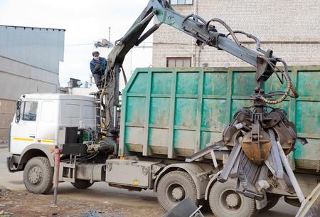 camion grua: Cargador de la m�quina con el cuchar�n Cangrejo hidr�ulico sube Residuos de Acero Foto de archivo