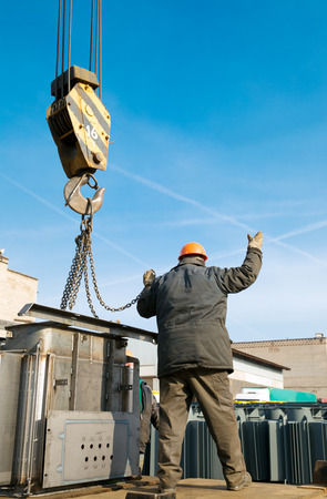 Industrial worker gesturing during loading and unloading cargo works with crane