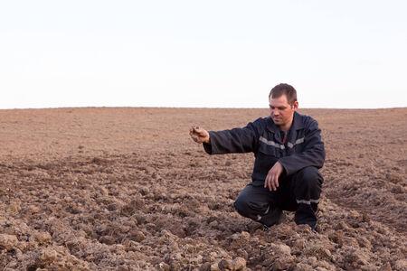siembra: Hombre del granjero en campo de cultivo mirando el suelo