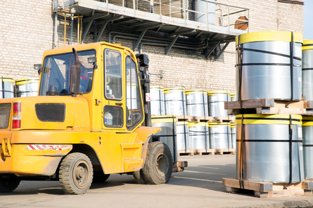 Forklift stacker transporting steel roll with pallet outdoors  photo