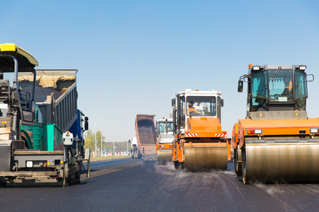 Asphalting construction works with commercial repair equipment road crews Foto de archivo
