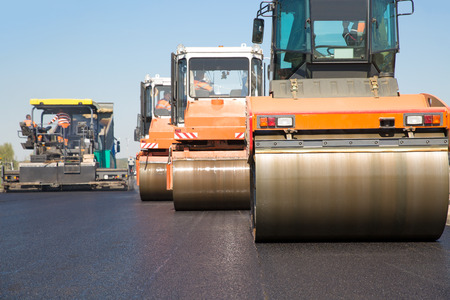 Pneumatic steam road rollers machines compacting fresh asphalt during highway construction works on tracked paver equipment background Foto de archivo