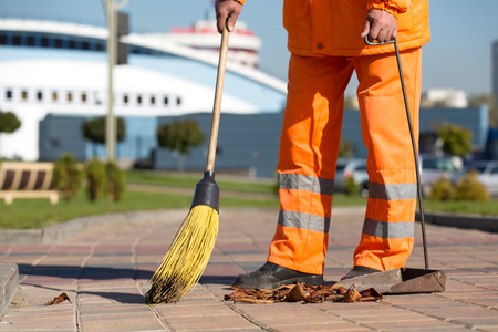 Street sweeper cleaning city sidewalk with broom tool and dustpan 스톡 콘텐츠
