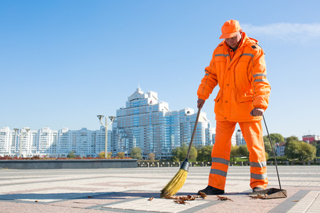 Man street sweeper cleaning city sidewalk with broom tool and dustpan