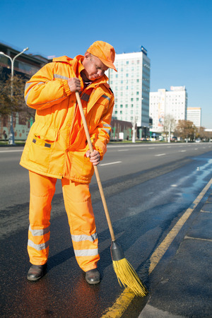 clean street: Man road sweeper worker cleaning city street with broom tool