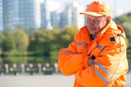 paysagiste: Travailleur de l'homme caucasien positive au fond bâtiments de la ville