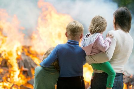 vagabundos: Familia de la madre con los niños en la quema de fondo casa