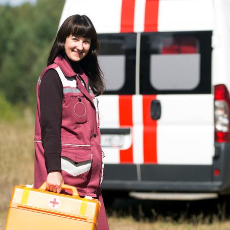 cruz roja: Feliz mujer paramédico con el caso en ambulancia máquina fondo