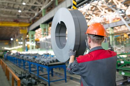 Factory worker transporting transformer steel cargo with workshop rail mounted gantry crane