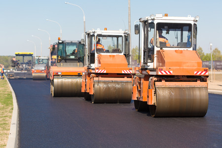 vibration machine: Intelligent Compaction for Asphalt Concrete Surface with Road Crews Rollers during Road Construction Works Stock Photo