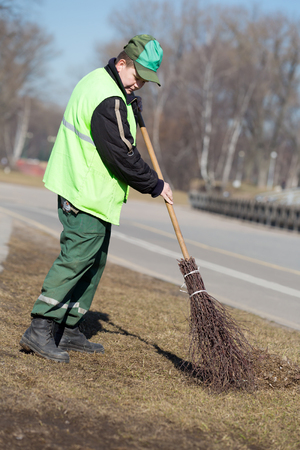 sweeper: Street Sweeper cleaning walkway in city park with broom tool