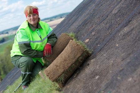 paysagiste: travailleuse Paysagiste pose laminé gazon gazon pour une nouvelle pelouse sur une pente inclinée