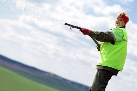 paysagiste: Paysagiste femme jardinier pelouse avec un tuyau d'arrosage Banque d'images