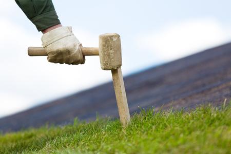 paysagiste: Paysagiste fixation des travailleurs roula gazon gazon sur le sol pour une nouvelle pelouse avec bâton de bois et outil de marteau Banque d'images