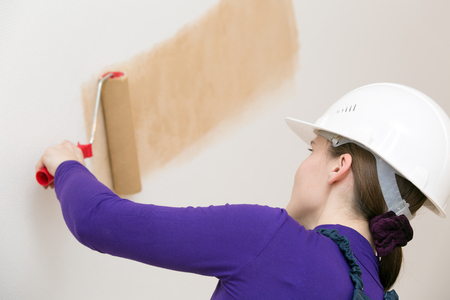 priming paint: Female house painter worker drawing wallpaper with painting roller tool in new apartment Stock Photo
