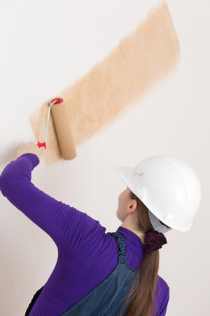 priming paint: Female decorator or house painter worker painting wallpaper with painting roller tool in new apartment
