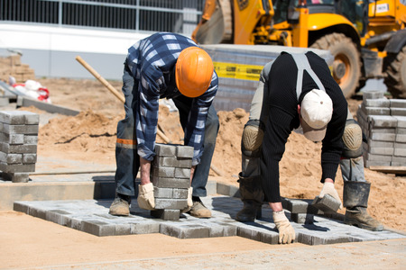 Two construction workers installing paver bricks during city road works
