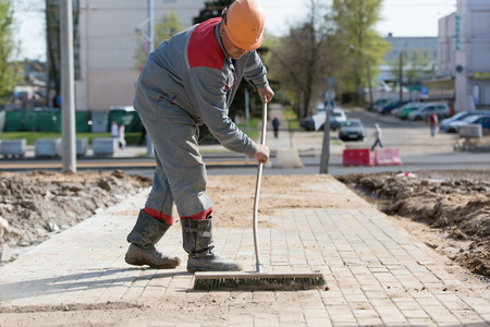 Construction worker grouting dry sand with brush into paver bricks joints during road works Standard-Bild