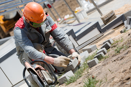 cut off saw: Construction worker marking cobblestones for cutting with petrol disc cutter equipment