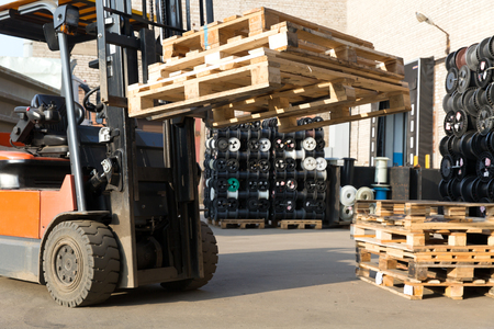 stacker: Factory Forklift Truck Stacker Transporting Pallets at Plant Warehouse