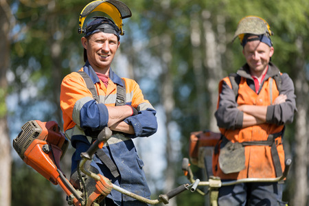 Happy professional garden workers with petrol string trimmers outdoors Stockfoto