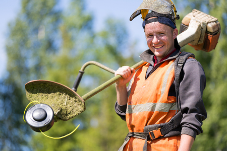 Portrait happy gardener or road landscaper man worker with gas grass trimmer equipment Stock Photo