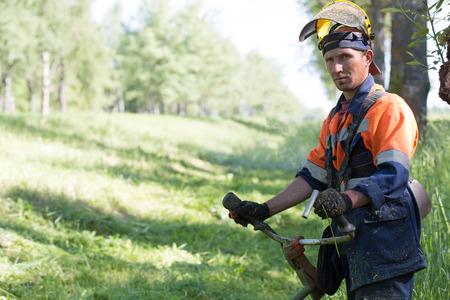 Trabajador del hombre Retrato paisajista durante el corte de hierba con gas de cadena de mano de equipos de corte