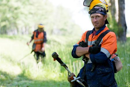 paysagiste: Portrait homme paysagiste positif travailleur de poche équipement chaîne de coupe de gaz lors de travaux de l'équipe de coupe de l'herbe Banque d'images