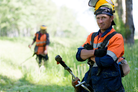 Portrait positive landscaper man worker with gas handheld string trimmer equipment during grass cutting team works