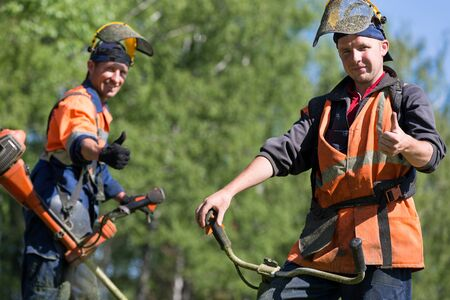 grass cutting: Happy road landscapers workers with string trimmers during grass cutting team works gesturing ok Stock Photo