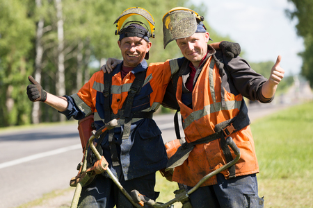 Happy road landscapers workers with string trimmers during grass cutting team works gesturing ok outdoors