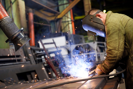 Manufacture worker welding metal at factory workshop with flying sparks