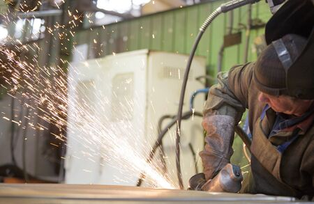 Metalworking industry: factory welder worker grinding steel sheet with flying sparks in workshop