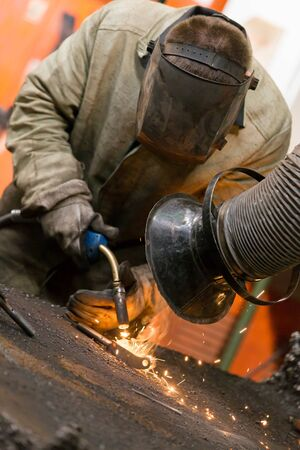 Manufacture worker welding metal at factory workshop with flying sparks and extraction smoke Imagens