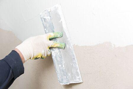 Builder indoor worker plastering wall with spatula trowel tool