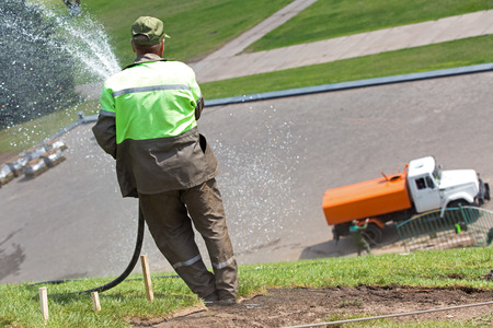 spaying: Gardener metropolitan administration worker watering lawn grass by water tanker truck