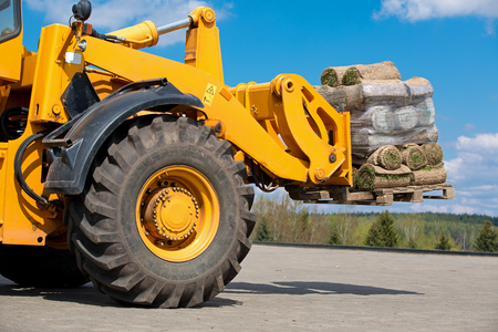 Wheel loader machine transportation pallet with green grass lawn rolls cargo