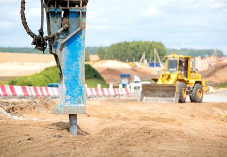 Large jackhammer crushing asphalt paving during road construction works on a wheel loader machine background